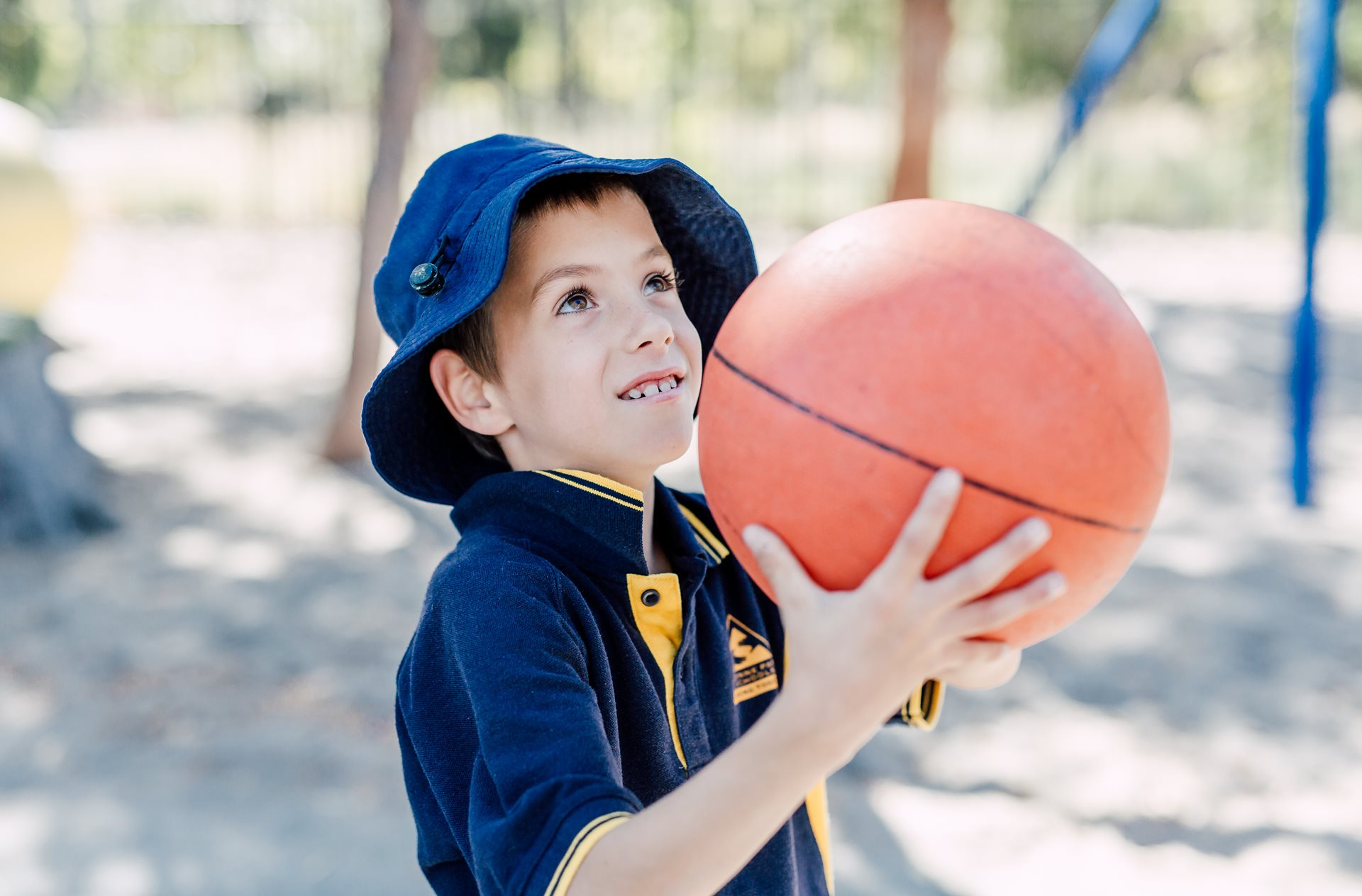 Child playing basketball outdoors at school mates
